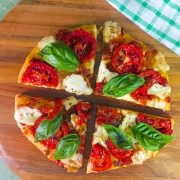 4 slices of a round Margherita Pizza/ Tomato Mozzarella Pizza with bright red tomato and fresh green basil leaves on a brown cutting board, with a green and white checked napkin to the side