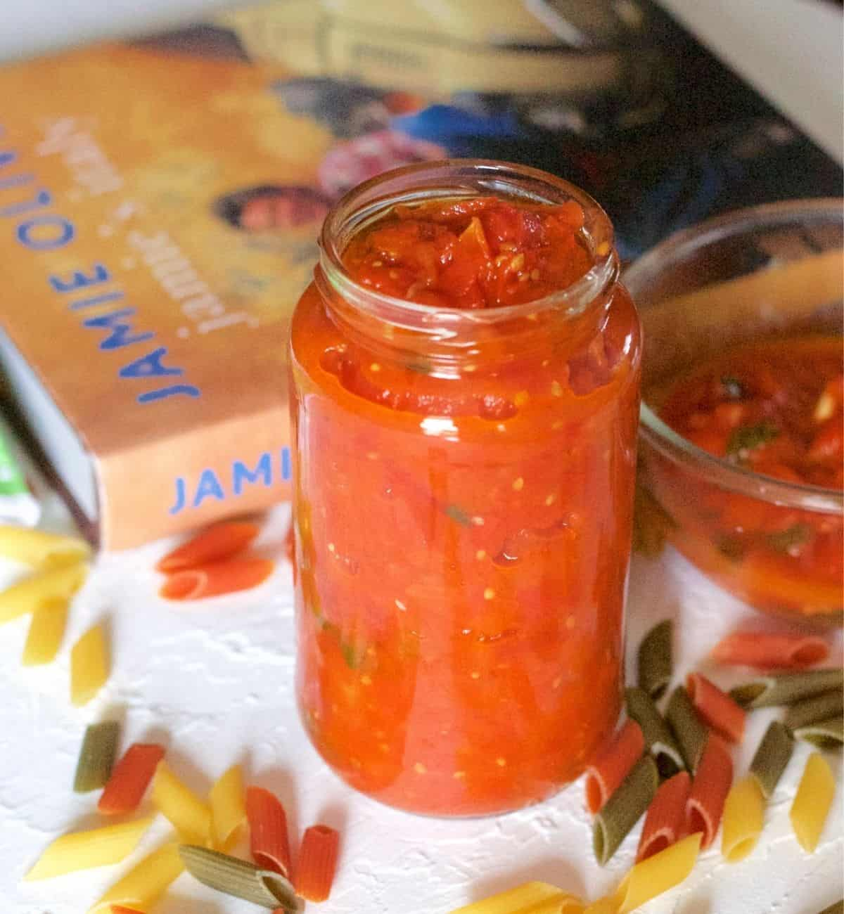 Orange red tomato basil pasta sauce in a tall glass jar with a yellow/orange covered cook book in the background. A bowl of sauce on the right and coloured penne pasta scattereda all around