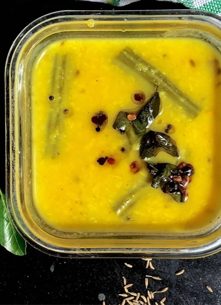 Bright yellow easy vegetable Kootu for the new Mom in a square glass bowl. Slices of green drumstick on the surface of the lentils, and a dark brown tempering of cumin, mustard, fenugreek and curry leaves on top