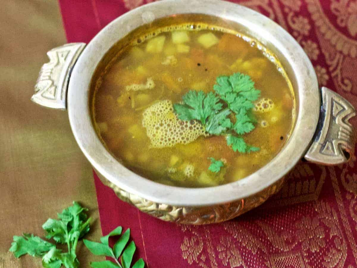 PIneapple rasam, a pale mustardy yellow coloured soup like liquid in a brass bowl,with coriander leaves as garnish. Resting on a red and olive green silk fabric