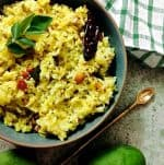 Yellow Raw mango rice or mangai sadam from grated seasonal raw green mango, seasoned with mustard, peanuts, dry chili and curryleaves, in a green bowl wiht an arrow shaped brass spoon on one side, a green mango and white and green checked napkin above