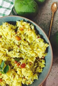Bright yellow raw mango rice seasoned with peanuts, curry leaves, lentils,mustard seeds, in a green bowl. A brass spoon seen to the right and part of a checked green on white napkin to the left