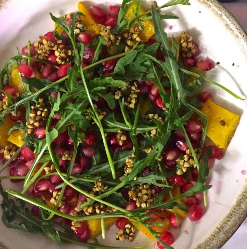 Yellow Roasted Pumpkin with green Rocket leaves and pink pomegranate on a white plate
