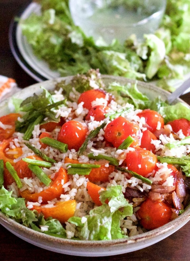 Bowl filled with red cherry tomatoes piled on a salad of brown rice, roasted tomato slices and greens. With a plate of greens and a glass bowl of lemon dressing in the background. Par of an orange edged white napkin on the left. All on a dark brown background