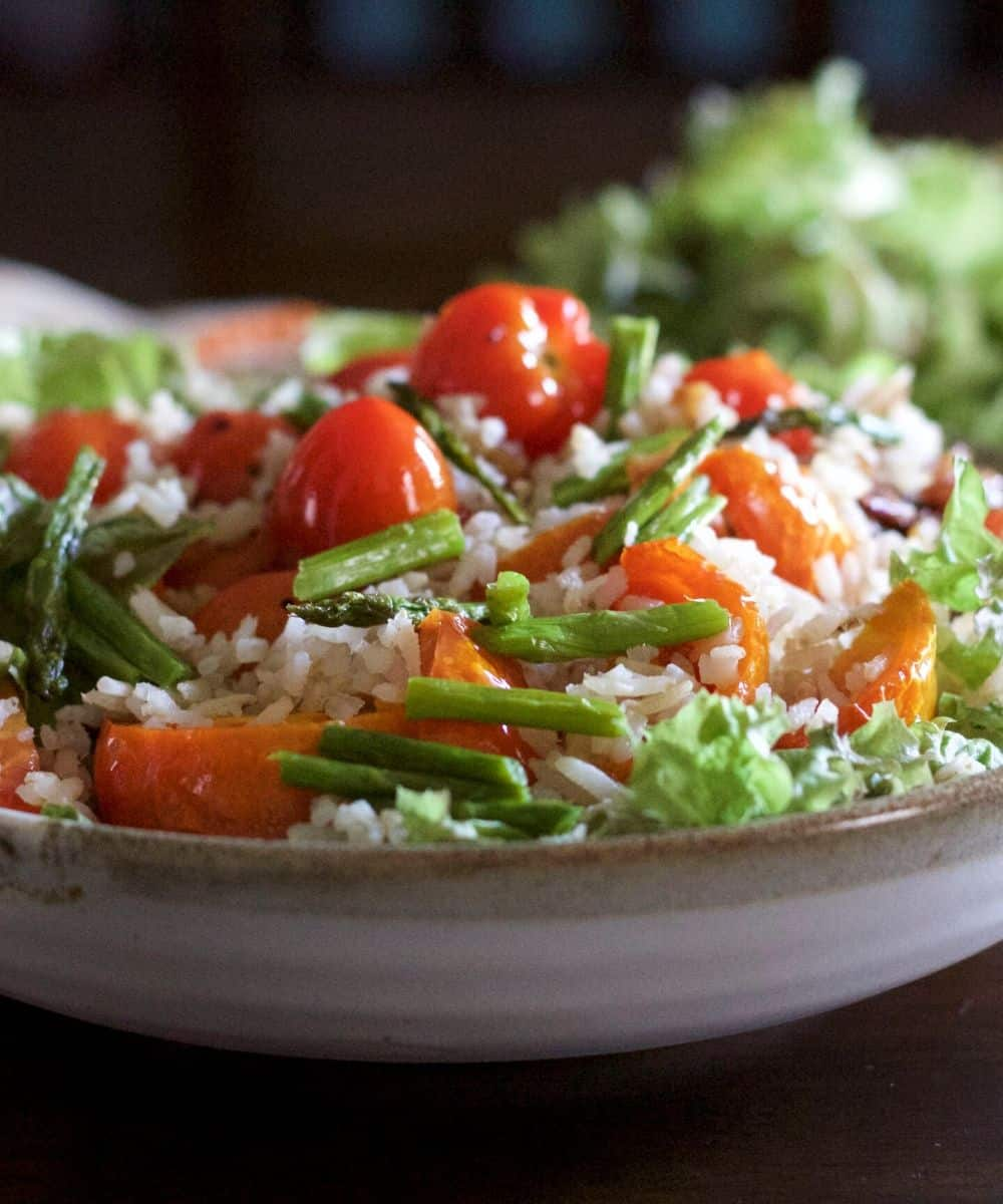 Large bowl of salad of tomato, brown rice, salad greens heaped on it. A blue rimmed plate of salad greens and a glass bowl with lemon dressing at the back and a orange dotted white napkin to the left