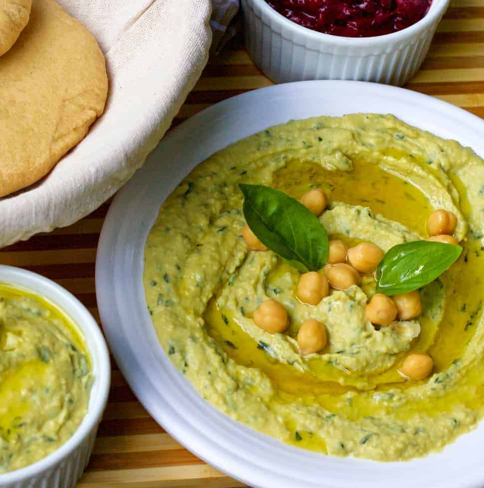 Pale green fresh lemon basil hummus garnished with chickpeas, olive oil and basil leaves, in a white plate
