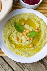 Greenish yellow Lemon Mint Basil Hummus Dip on a white plate, with chickpeas and basil leaves for garnish