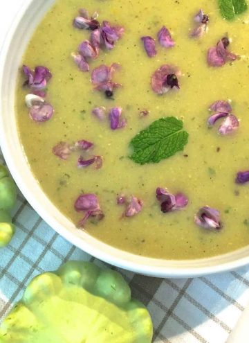 A white edged bowl of green yellow patty pan soup, garnsihed with fresh purple hyacinth flowers and fresh mint leaves. Two green patty pan squash seen on the thin brown striped white napkin in the foreground