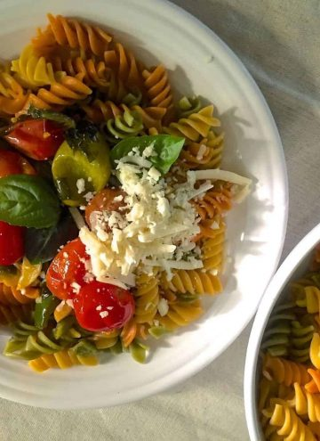 Colourful Rotini Pasta from juicy cherry tomatoes, garlic, fresh basil and spirally wholewheat pasta, on a white plate