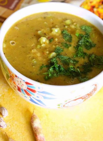 Mustard coloured lentil stew, Nourishing Masoor dal for the New Mom, in a white bowl patterned with red and blue, on a yellow background. Pink cranberry beans in the foreground and a red and orange covered cook book in the background