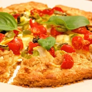 Whole wheat herbed patty pan squash tomato tart, sliced into wedged, with bright red cherry tomatoes and green basil leaves on top