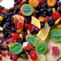 A colourful array of dry fruits, kiwi, pineapple, berries, citrus, papaya ready to be prepared for a Christmas cake
