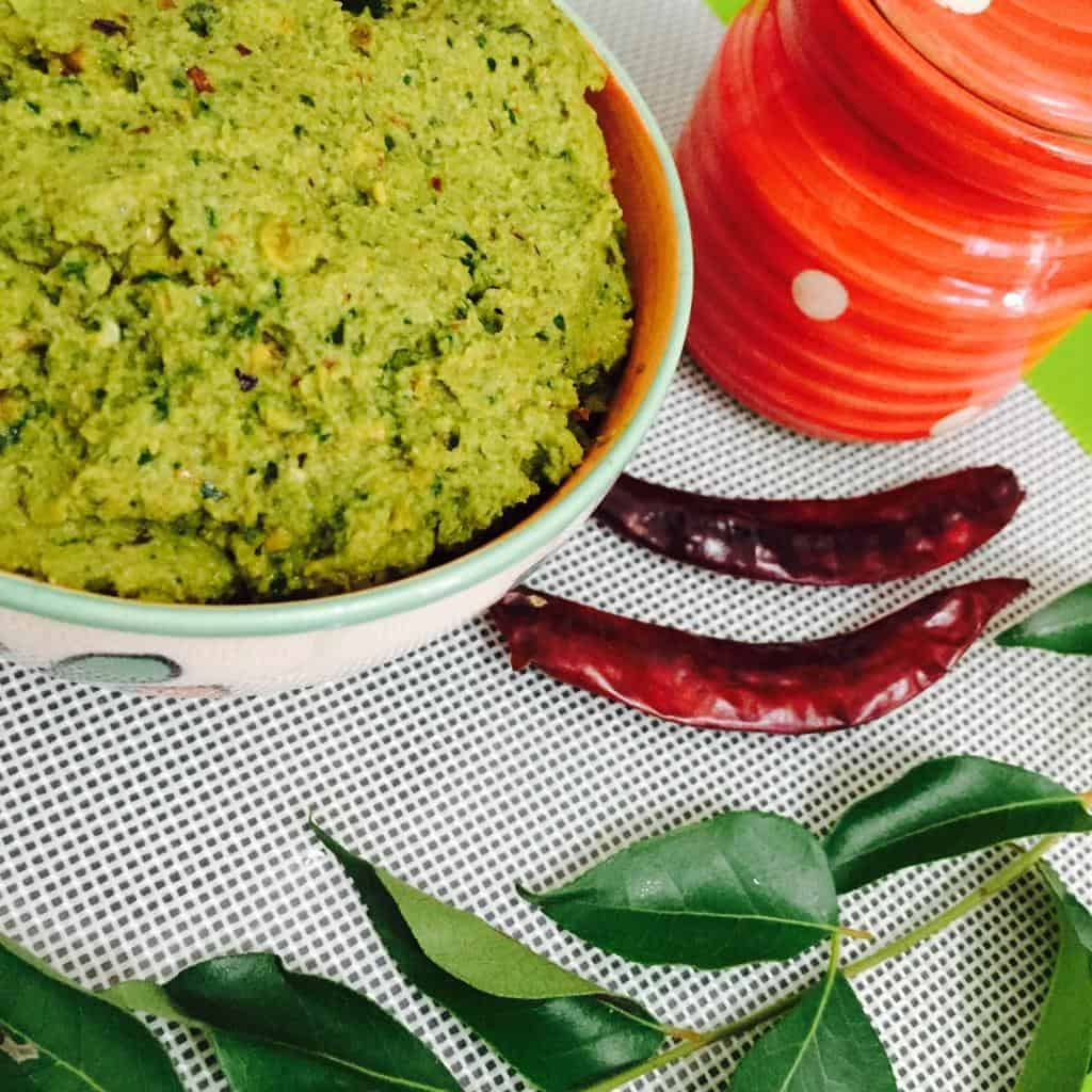A bowl of peerkangai thogaiyal or ridge gourd dal chutney, with a red jar, red chilies and green curry leaves alongside