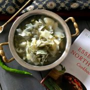 Oying Vegetable Stew from Arunachal Pradesh in NE India. Brass bowl with stew of cabbage, potato and beans with Cookbook and a green chilli by the side