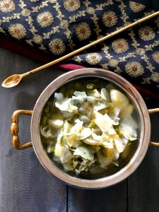 Brass bowl with handles with potato cabbage beans stew and a black and red silk cloth above with an arrow shaped spatula lying across