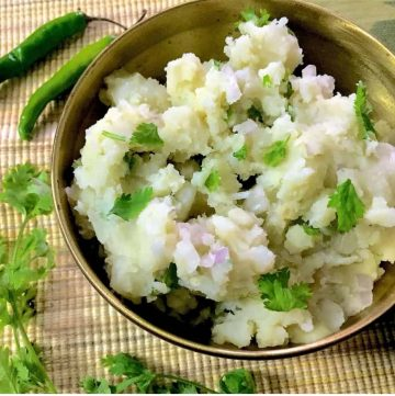Assamese Aloo Pitika - a brass bowl with mashed potatoes, cilantro, mustard oil, green chillies and onion on a mat, with green chillies and cilantro alongside