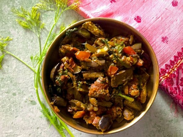 Baingan Badi Sabzi - curried slices of aubergine with black gram lentil fritters, turmeric, spinach, dill and Indian spices, in a brass bowl with dill leaves alongside and resting near a pink embroidered cloth