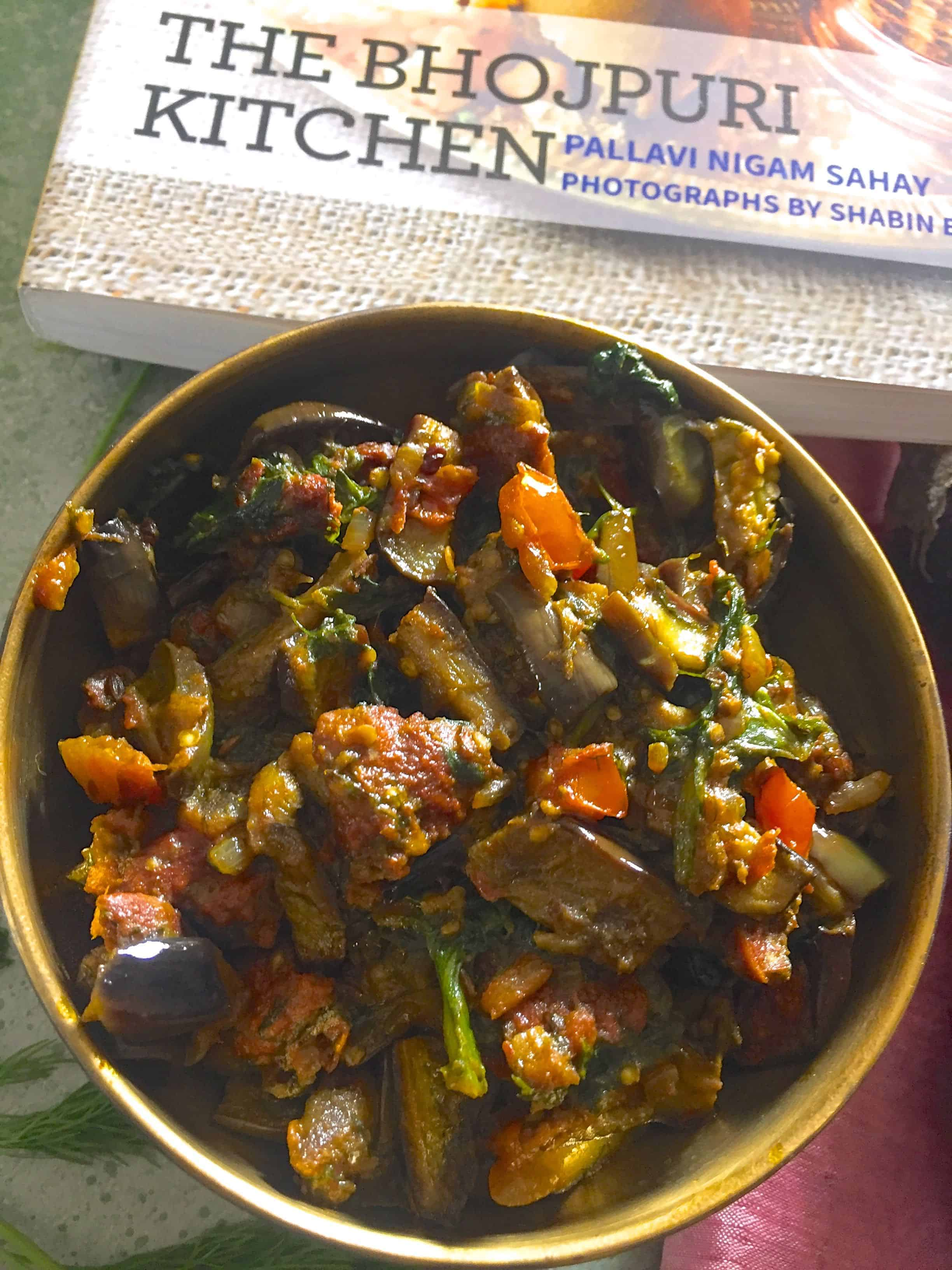 Brass bowl filled with brinjal curry with red tomatoes, lentil fritters and dill. A book on Bihari Cuisine in the background, a pale pink emroidered saree in the background