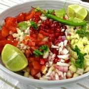 Kachumber Salad A colourful salad of chopped tomatoes, onion, carrot, cucumber and raw mango in a grey bowl garnished with pomegranates and green chilli