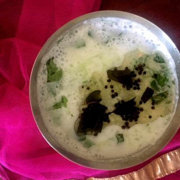 Neer Mor a mildly spiced and herbed buttermilk summer cooler served chilled in a tall glass with cucumber garnish and tempered with mustard seeds and curry leaves