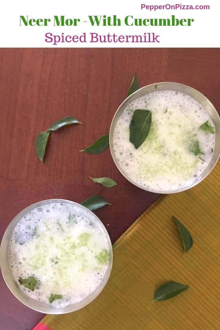 2 tall steel tumblers of white frothy Neer Mor a spiced, herbed buttermilk summer cooler served chilled with cucumber garnish, tempering of mustard seeds, curry leaves on a brown background with curry leaves scattered around. https://www.pepperonpizza.com
