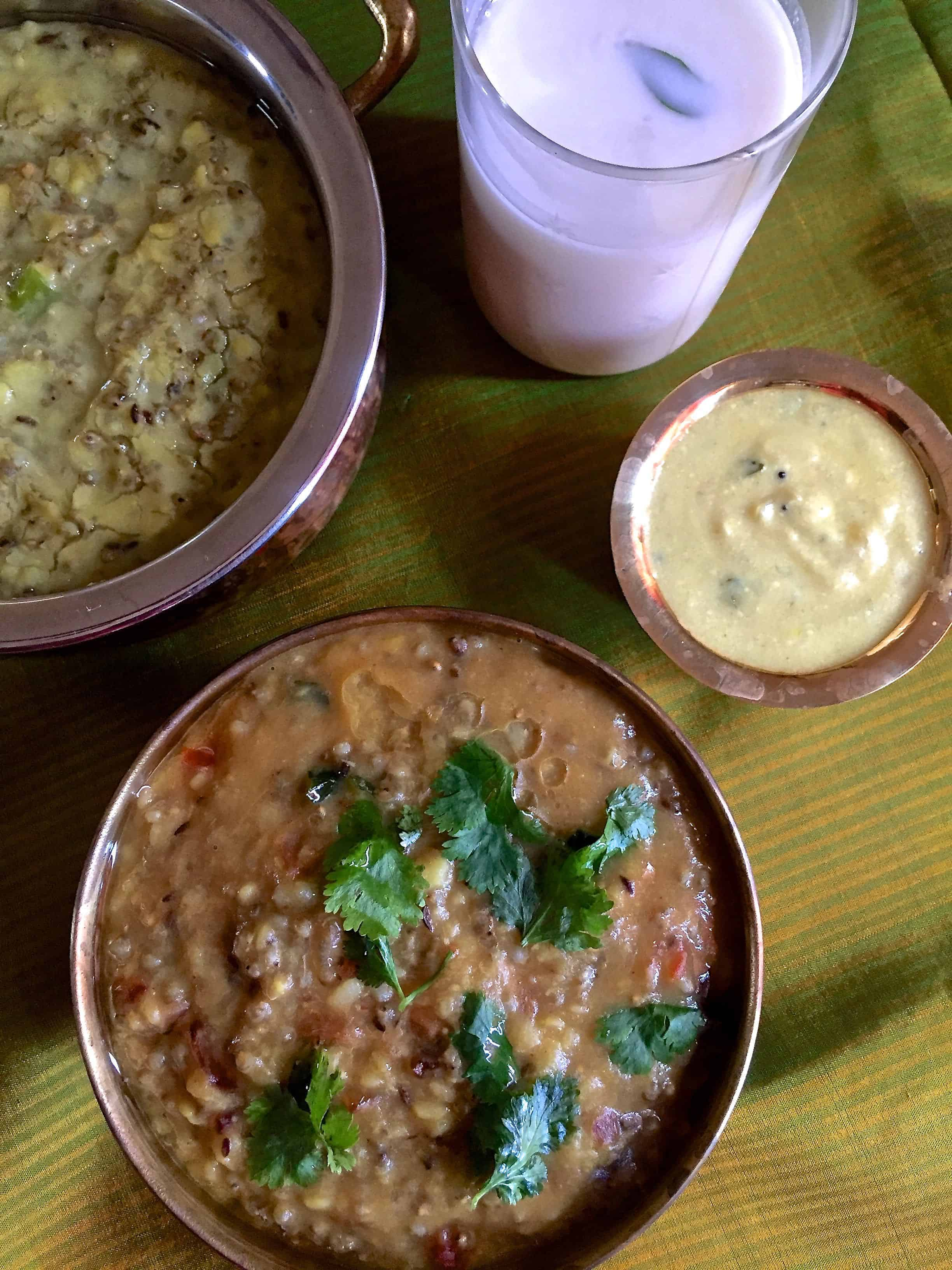 A bowl of greenish yellow cooked millets and lentils with a glass of buttermilk and the edge of an orange book at one corner