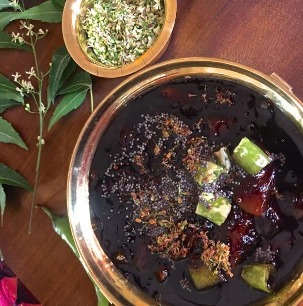Raw Mango Pachadi for Tamil New Years Day in a brass bowl with a tempering of chilies and mustard seeds and garnish of Neem flowers