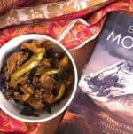Kashmiri Green Apple Brinjal Curry or Bom Chount Wangan Sabzi of fried eggplant and green apple cooked in spices, in a white bowl with a silk stole and book on the Himalayas alongside