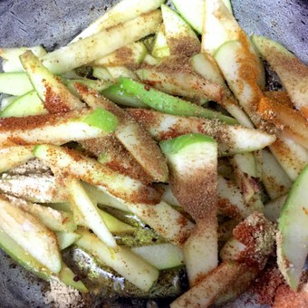 Spices and salt added to the green apples in the pan
