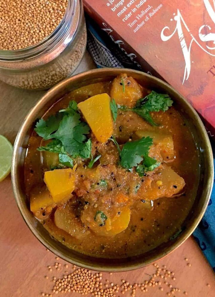 Panch Phoron Kaddu Sabzi, chunks of spiced pumpkin curry in an iron pan with a red book on Emperor Ashoka on one side and yellow mustard and cilantro scattered below