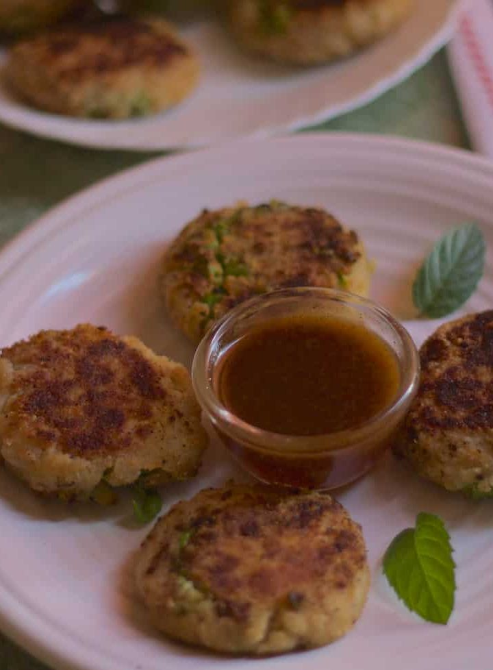 White plates with little brown aloo tikkis or potato patties, with a little cup of red tamarind chutney and mint leaves