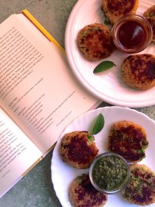 Two white plates of aloo Tikki (potato patties) with an open book showing the recipe from which they are prepared