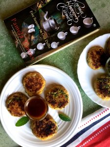 4 aloo tikki or potato patties on a white plate with mint leaves between and a book Korma Kheer Kismet alongside