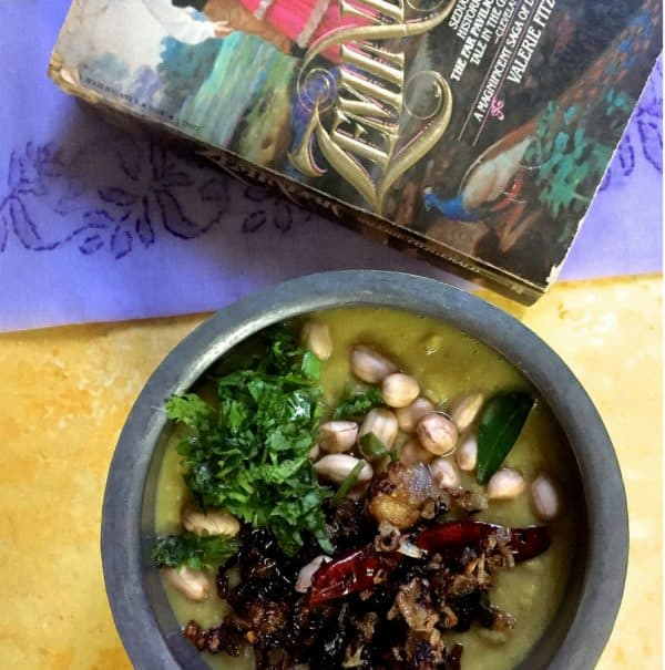 A bowl of Arhar ki Khatti Dhal on a yellow background, a mauve Lucknowi chikan saree and a novel based in Lucknow