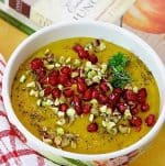 Curried Roasted Pumpkin Soup with apples and Indian spices including turmeric, in a white bowl and a garnish of ruby red pomegranate arils and crushed pista nuts