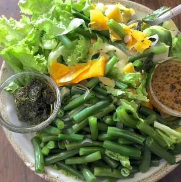 A bowl of beans, greens and green and yellow zucchini ribbons with green pesto and orange citrus dressing in tiny cups on either side of the bowl comprise the Pesto Green Bean Ribboned Zucchini Salad with Citrusy dressing