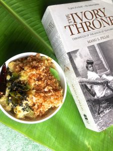 Raw Banana Varutha Erissery in. white bowl on a green plantain leaf, with a book on Kerala History alongside