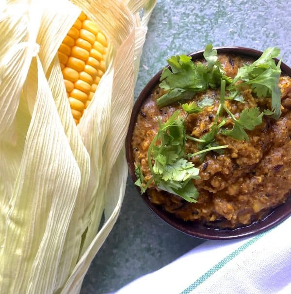 Makai ki sabzi, a spicy corn curry. Served in a bowl garnished with coriander leaves and with a corn cob on the side