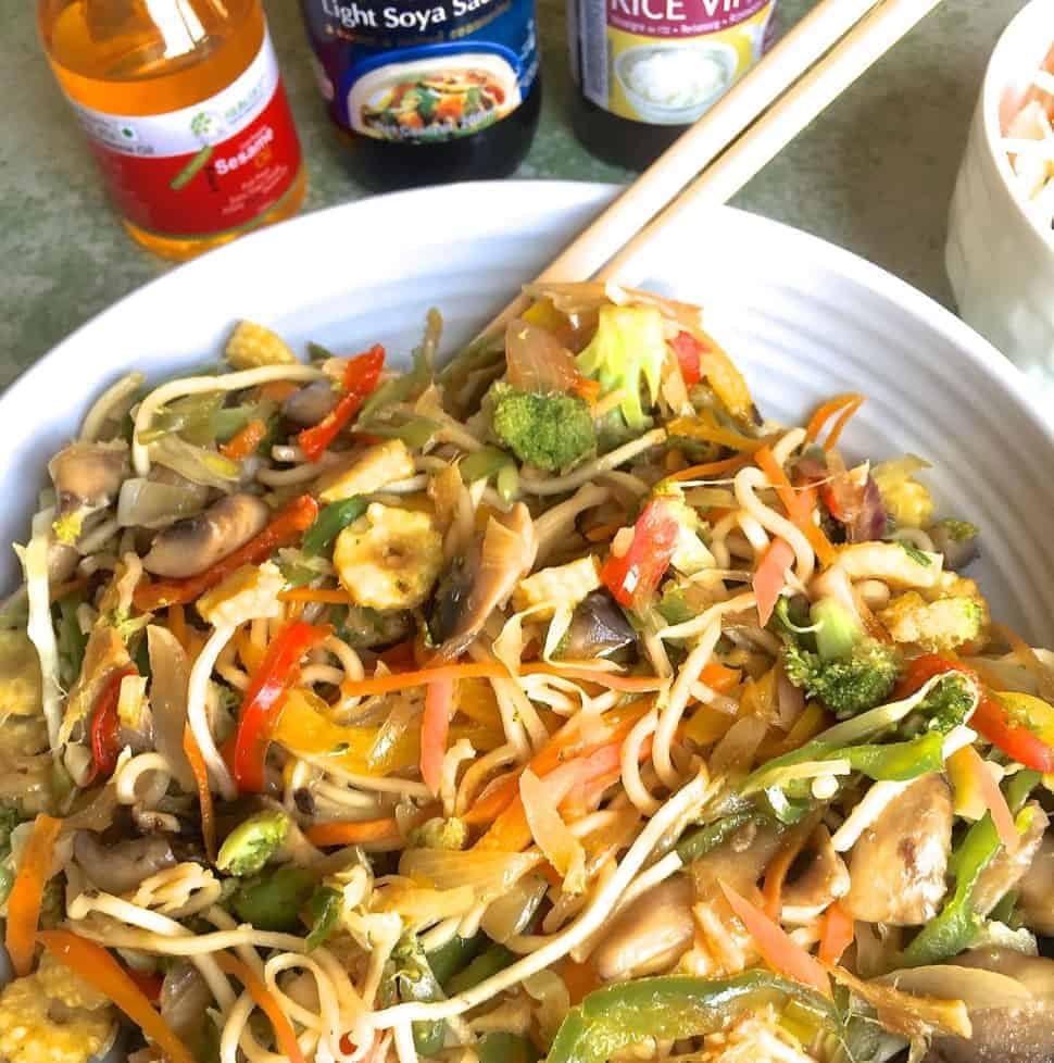 Stir fried vegetable noodles in a bowl with a pair of chopsticks and a glimpse of bottles of sesame oil, rice vinegar and soy sauce for the seasoning
