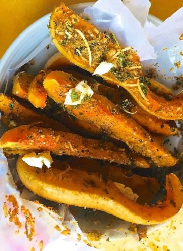 Baked squash liberally crusted with parmesan and herbs.