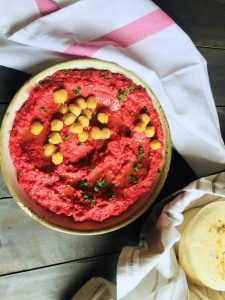 Bright bowl of roasted beetroot humus garnished with cooked chickpeas and olive oil, and with a basket of pita bread by the side
