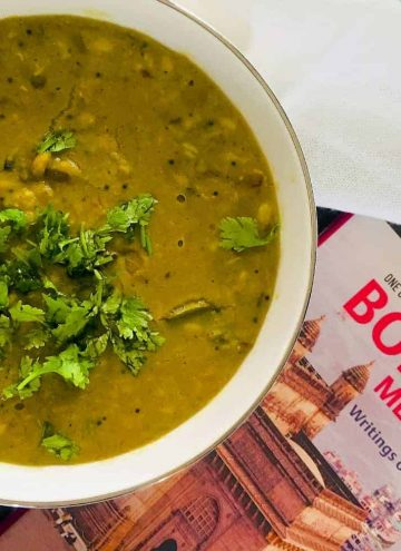 Comfort food Maharashtrian Amti Dal with Goda Masala in a large bowl with coriander leaves garnish and a book on Mumbai alongside