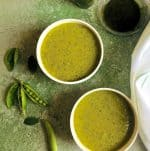 Warming Pea Mint Basil Soup in two white bowls on a green background with split pea pods, mint and basil leaves by the side and a white napkin and a bowl of basil oil seen alongside