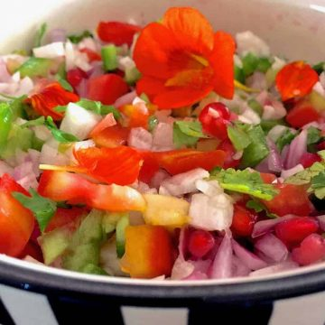 Rainbow salad with red nasturtium, chopped sweet peppers, tomato and other vegetables and greens in a yellow white and black striped bowl