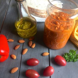 Roasted red pepper and tomatoes with almond and bread in an orangey Spanish Romeso Sauce in a jar, with olive oil, almonds, tomatoes, pepper and parsley scattered around and some bread just behind