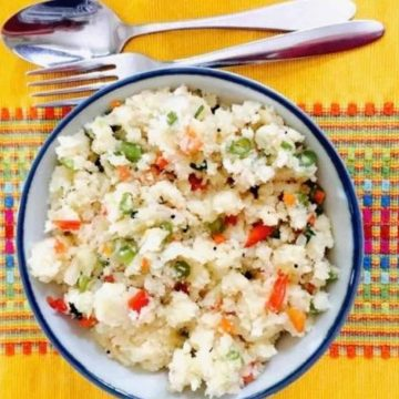 Hot tasty breakfast Vegetable rava Upma with semolina flour. A bowl of Upma on a yellow patterned runner with a steel fork and spoon above