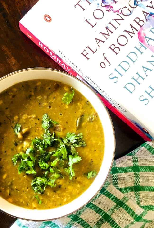 A bowl of Amti Dal with Goda Masala,with a checked green napkin below and a book on Bombay alongside