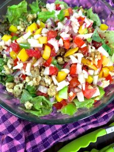 Colourful rainbow salad of fresh vegetables in a citrusy dressing