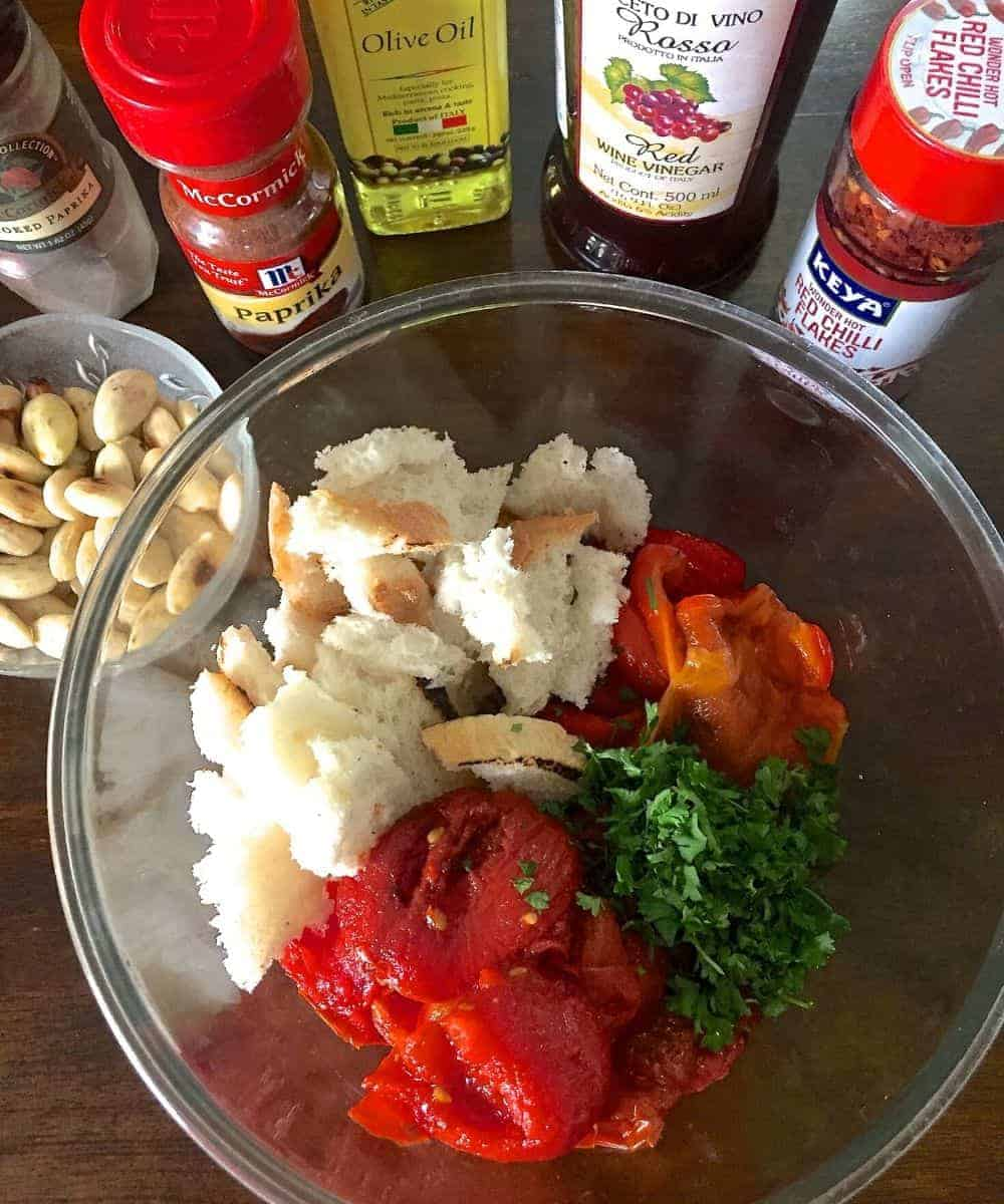 Ingredients for Spanish Romesco Sauce: Glass bowl with bread, roasted red peppers, parsley and tomatoes, with blanched peeled almonds in another bowl and other ingredients in bottles in the background