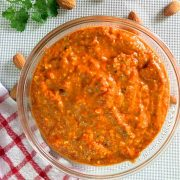 Glass bowl filled with bright orange thick Spanish Romesco Sauce with flecks of green from parsley. Almonds and parsley scattered in the background and a red and white checked cloth to the left
